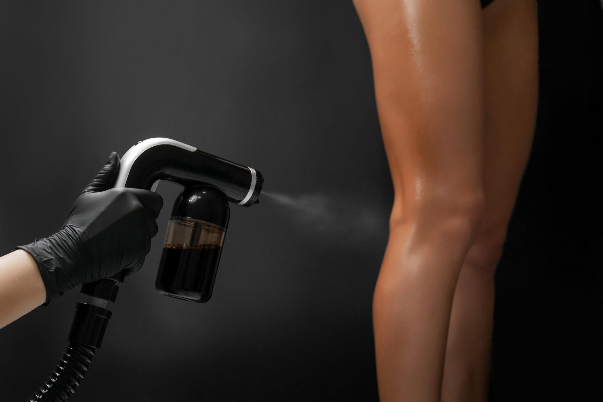 En kvinna får en spray tan-behandling