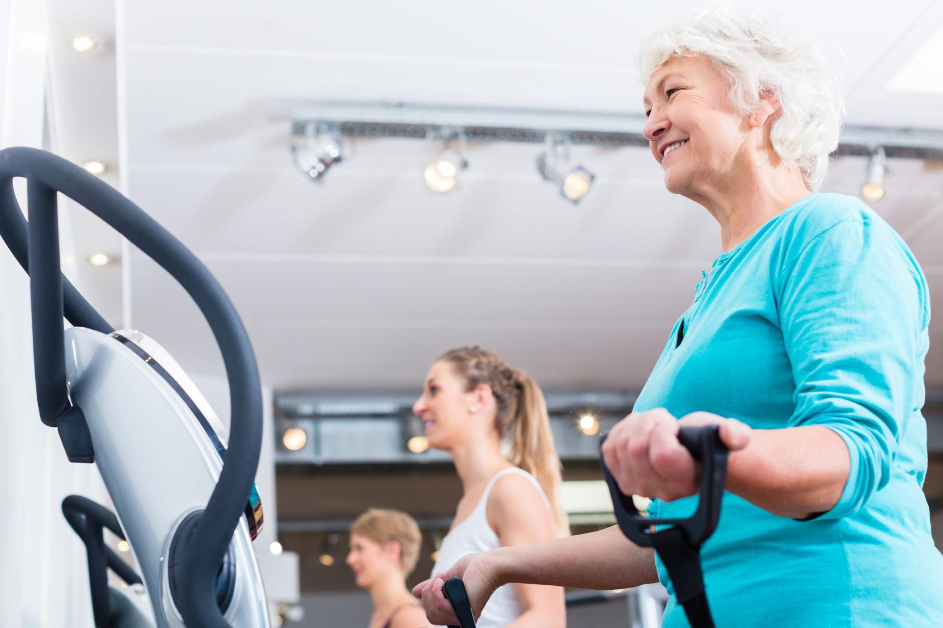 En äldre kvinna tränar glatt med vibrogym